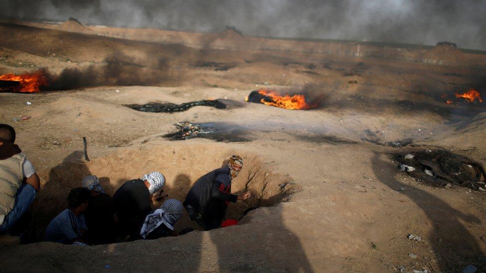 Manifestantes entre las llamas en las protestas en la frontera de Gaza con Israel.