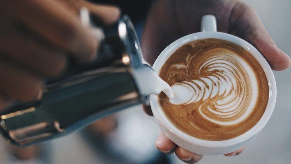 Taza de latte con diseños hechos con el café sobre la leche