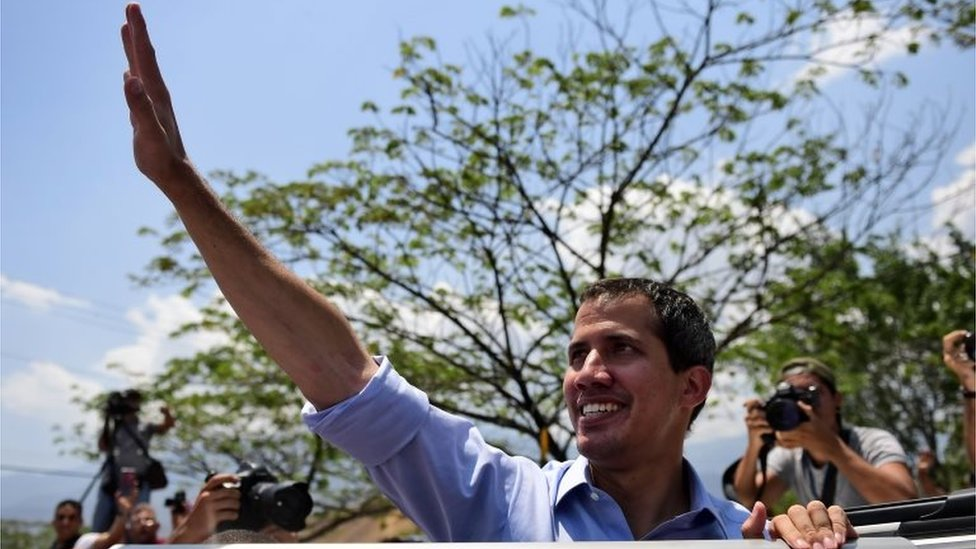 Venezuelan opposition leader and self-declared president Juan Guaido waves to supporters during a rally in Guatire, Miranda state, Venezuela on May 18, 2019.