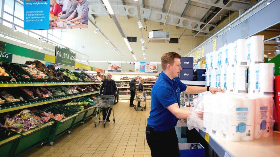 Aldi staff restock shelves at the supermarket in Altrincham, England