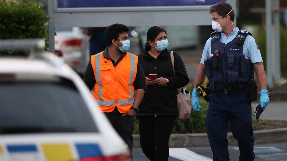 Policajac ispraća ljude iz Linmola do njihovih automobila posle napada ekspremiste koji je nožem napao šest ljudi