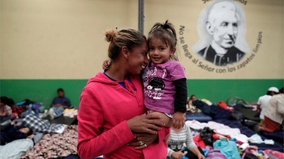 A Honduran migrant, part of a caravan trying to reach the U.S., carries her daughter at a migrant shelter in Guatemala City