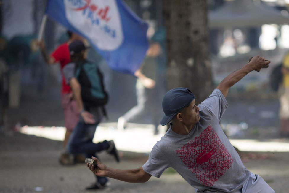 An anti-austerity protester throws a stone at police, outside the state legislature where lawmakers are discussing austerity measures in Rio de Janeiro, Brazil, Tuesday, 6 December