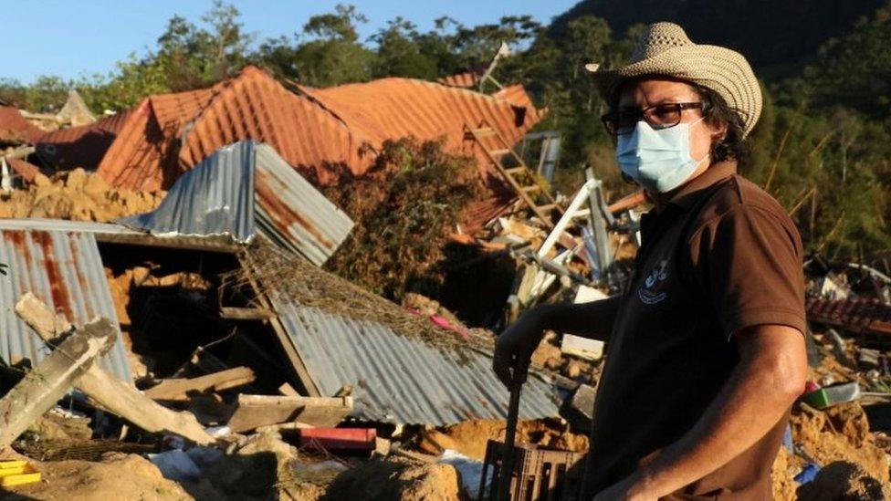 Persona frente a su casa destruida en Honduras.