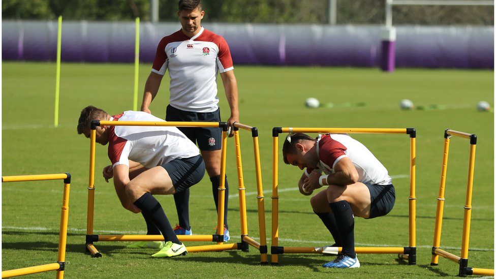 Owen Farrell (L) and team mate George Ford crouch under a hurdle watched by Ben Youngs during the England Rugby team training session