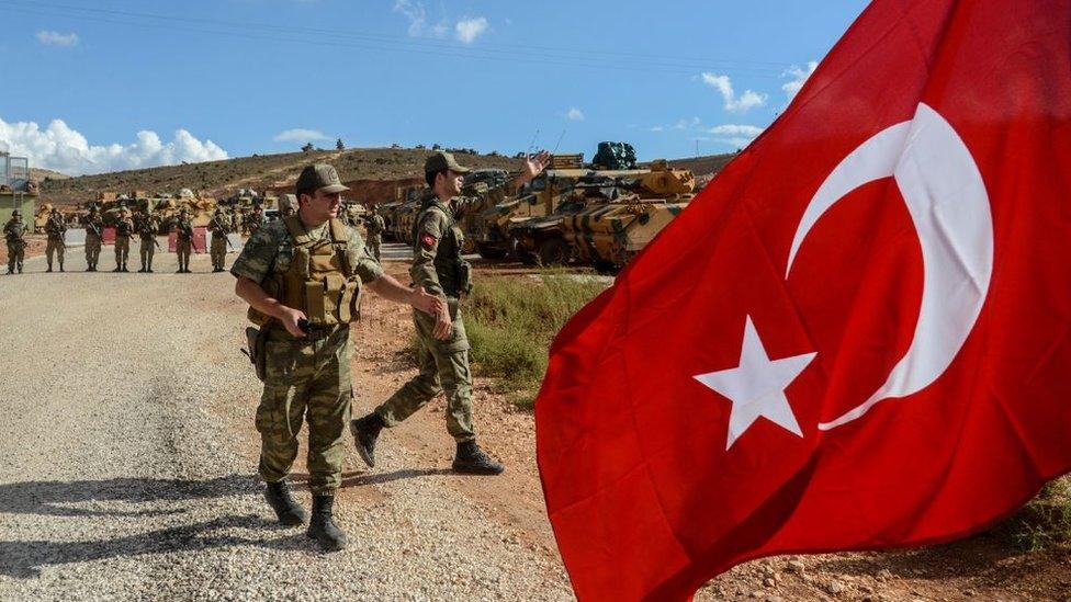 Militares y taques turcos con la bandera turca en primer plano.