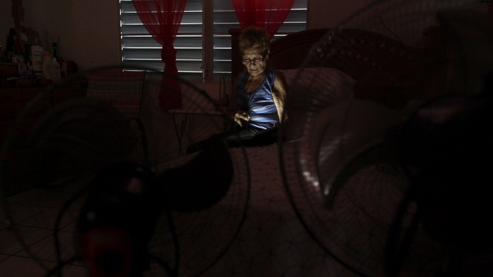 Irma Arroyo reads a book with a flashlight at her home without power, after Hurricane Maria hit the island