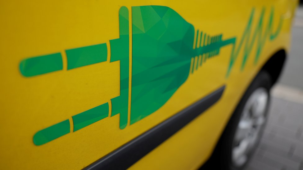 A power plug symbol is seen on an electric car