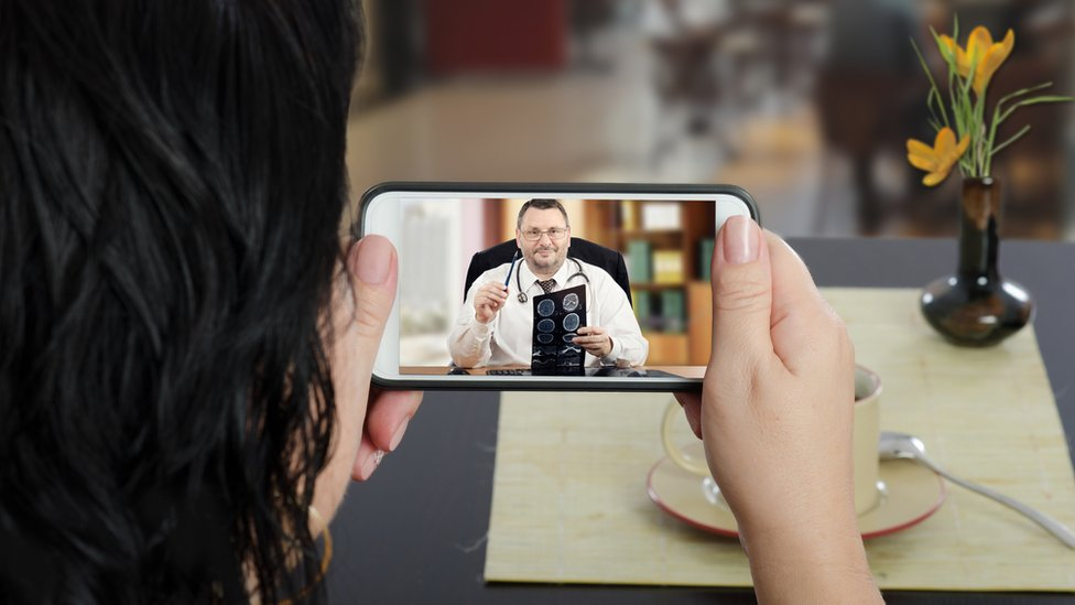 Woman consulting doctor via smartphone video