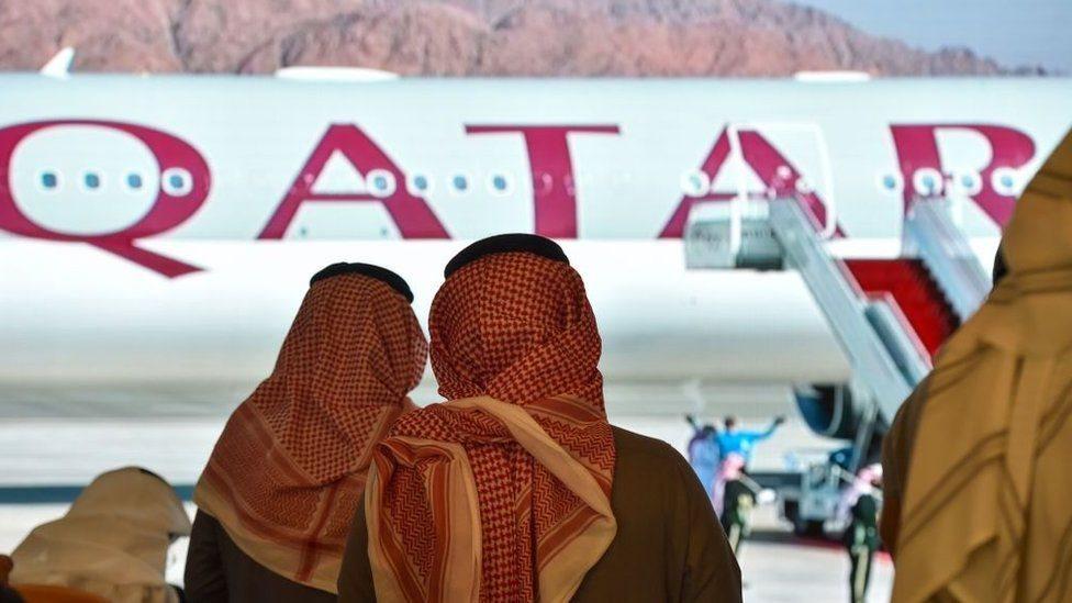 Foto archivo de dos mujeres viendo un avión de Qatar Airways
