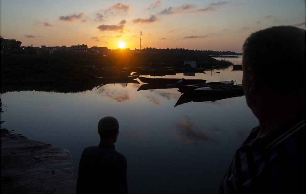 Men stand by boats as the sun is low in the sky in Al Maadea district of Behera Governorate.