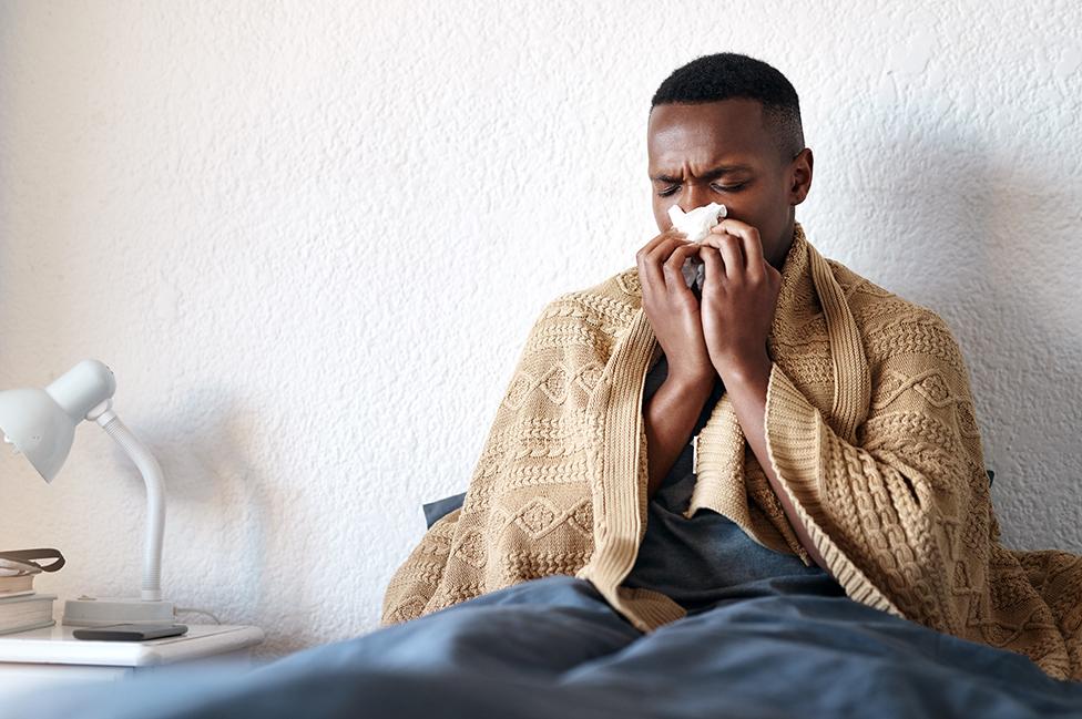 Un hombre en la cama soplándose la nariz