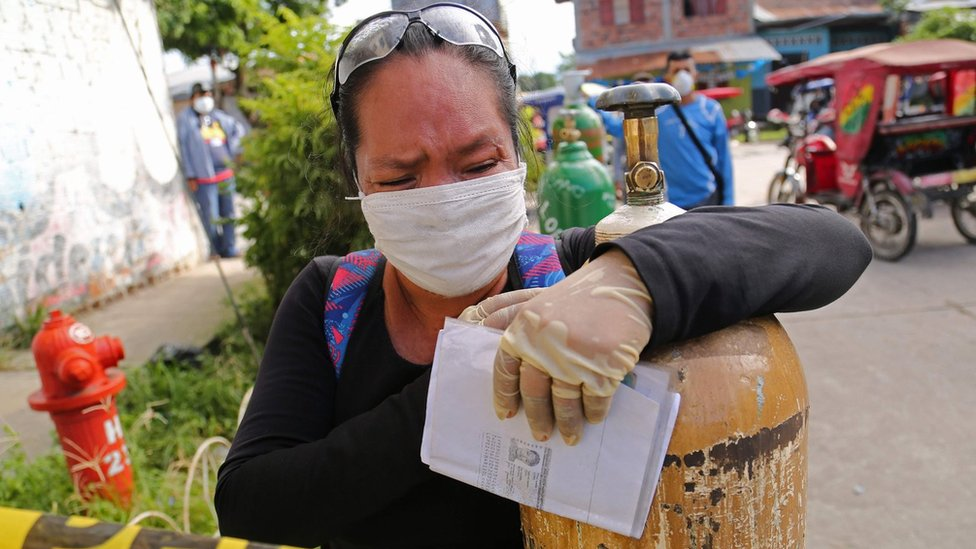 A relative of a COVID-19 patient queues to recharge oxygen tanks for their loved ones at the regional hospital in Iquitos, the largest city in the Peruvian Amazon, Peru
