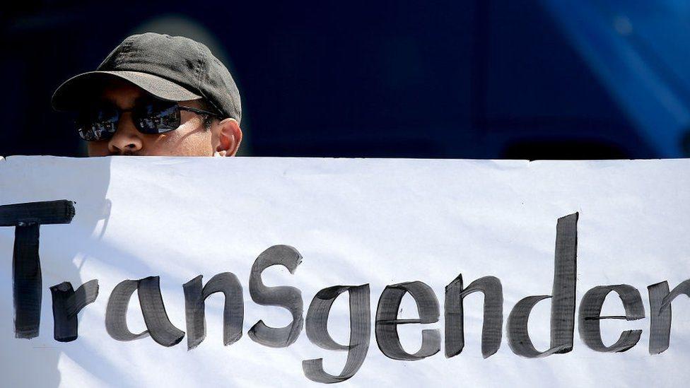 "Un manifestante sostiene una pancarta que dice ""transgénero""."