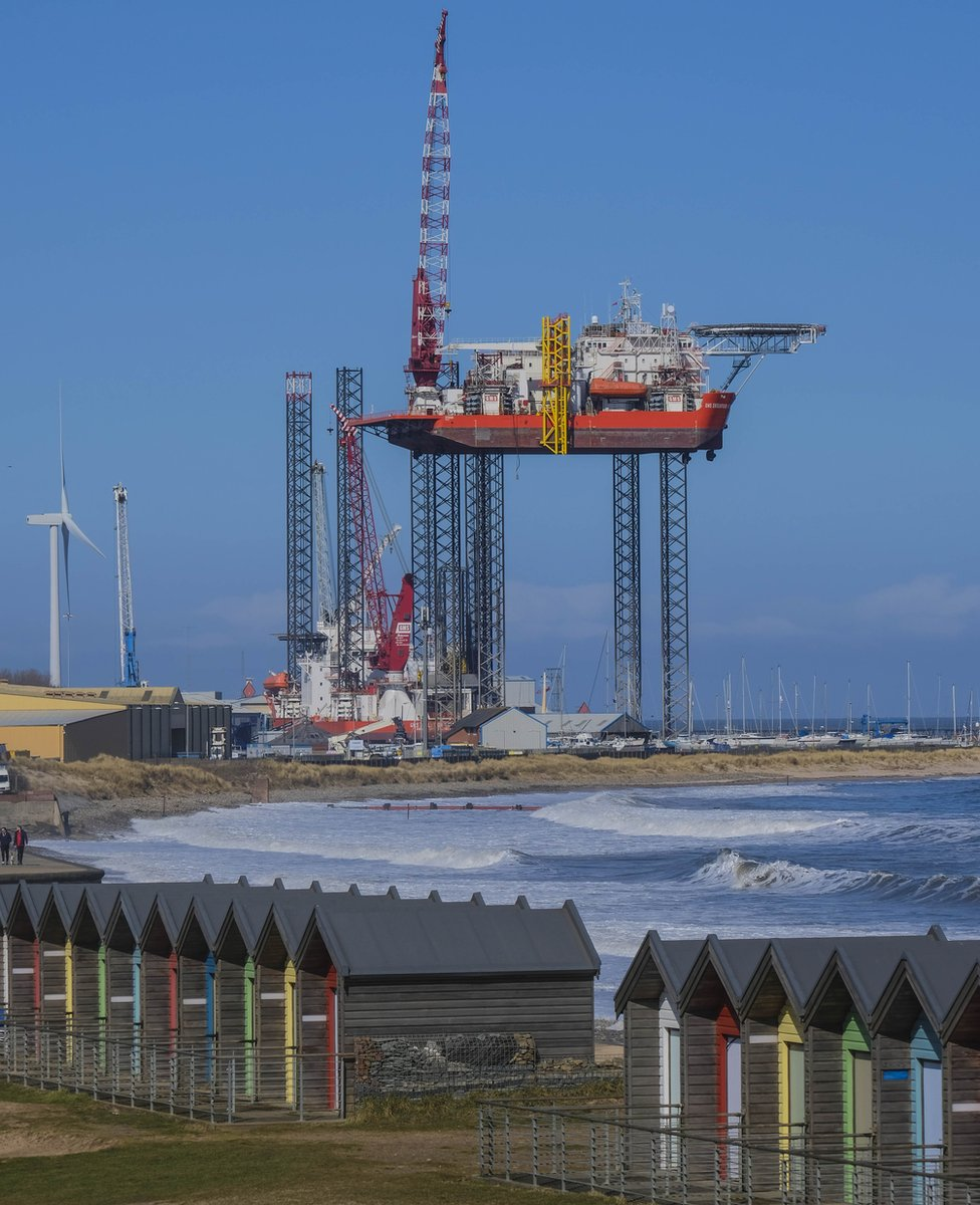 A coastal view of beach huts and an industrial structure