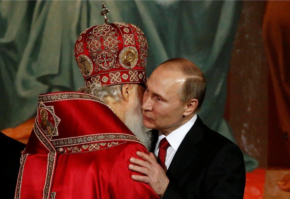 El patriarca Kirill, quien encabeza la Iglesia ortodoxa rusa, abraza al presidente de Rusia, Vladimir Putin, durante la misa de la Pascua ortodoxa, el 16 de abril de 2017.