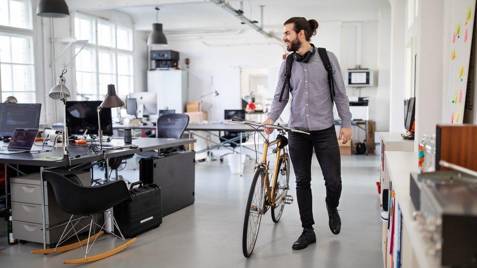 Joven con bicicleta en la oficina