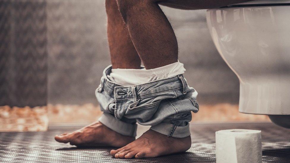 muškarac sedi u toaletu