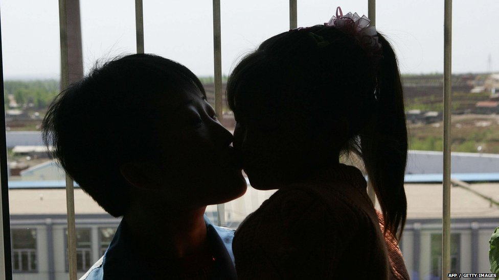 An inmate kisses her daughter during a celebration on Mother's Day at the Jilin Provincial Women's Prison 13 May 2007