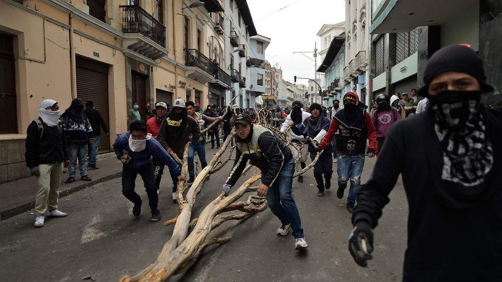 Manifestantes llevando un tronco seco por las calles de Quito.