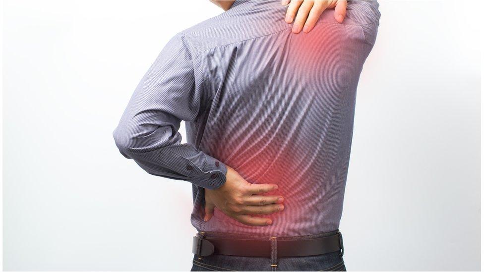 Homem com dor nos ombros e na lombar