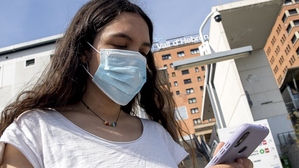 Una mujer con mascarilla frente al hospital Vall d´Hebron