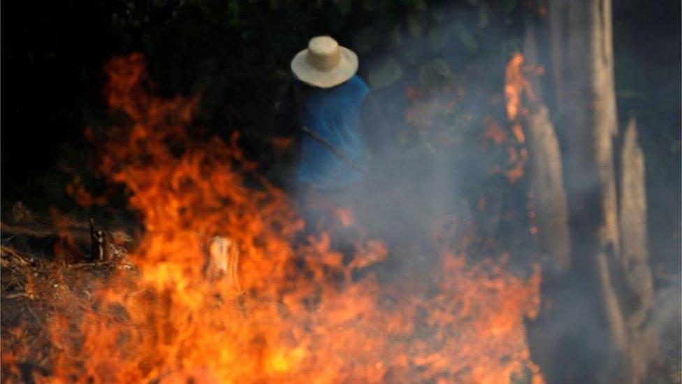 Hombre delante de un incendio en la Amazonía.