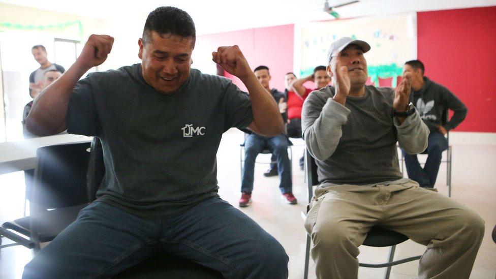 Mientras esperan en un albergue del Ejército de Salvación en Tijuana, estos migrantes celebran el buen desempeño del Tri.