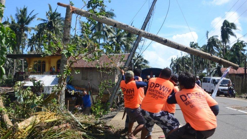 Los trabajadores tiran de un pilón eléctrico caído dañado a la altura del tifón Phanfone en la ciudad de Salcedo, en la provincia de Samar Oriental, el 26 de diciembre de 2019.