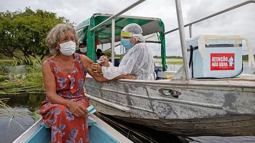 Profissional da saúde aplica vacina no braço de mulher, que está num barco