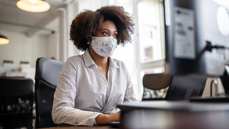 Mujer con mascarilla en oficina
