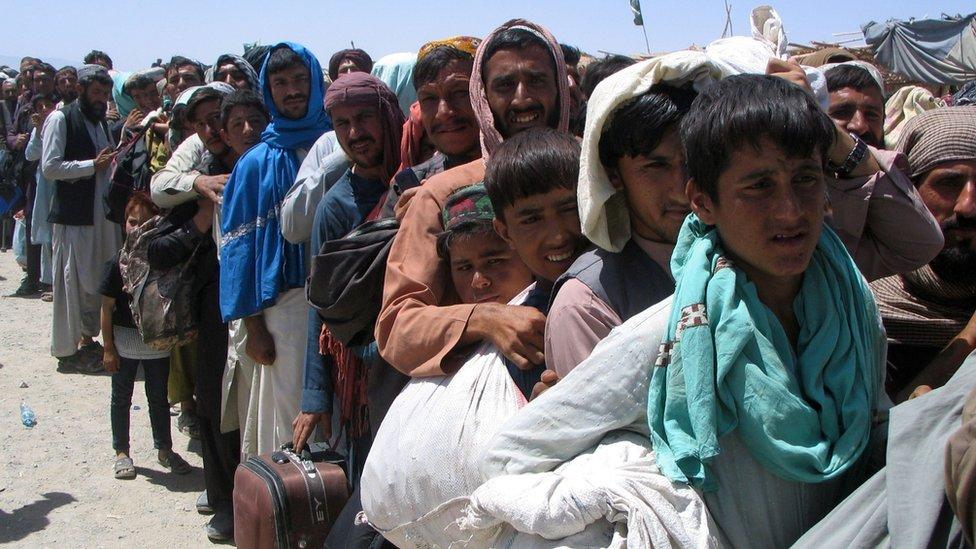 Civiles afganos esperan cruzar la Puerta de la Amistad en el pueblo fronterizo de Chaman, Pakistán, 13 de agosto de 2021