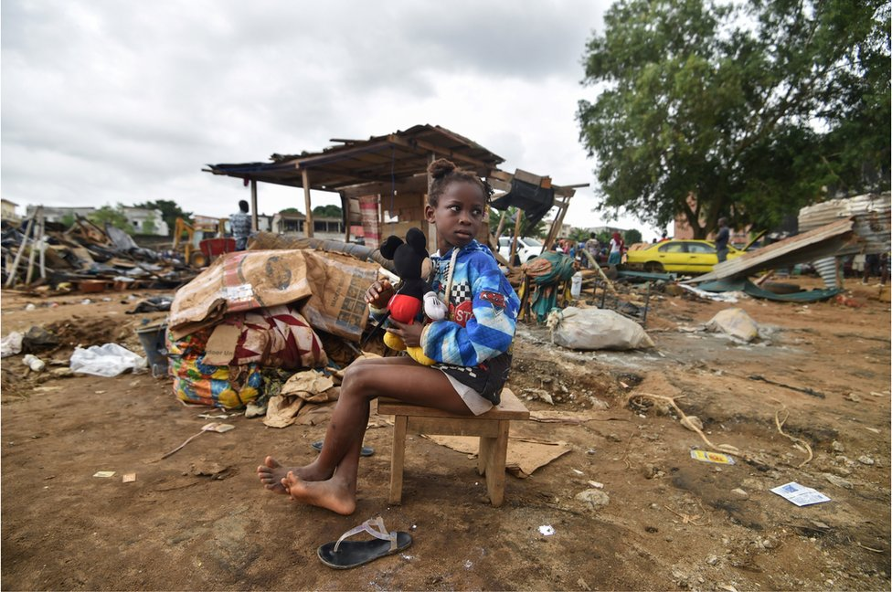 A young girl, holding her toy, looks on as she sits on a chair, after her shelter at a small neighbourhood at the district of Cocody in Abidjan was destroyed, on June 23, 2018