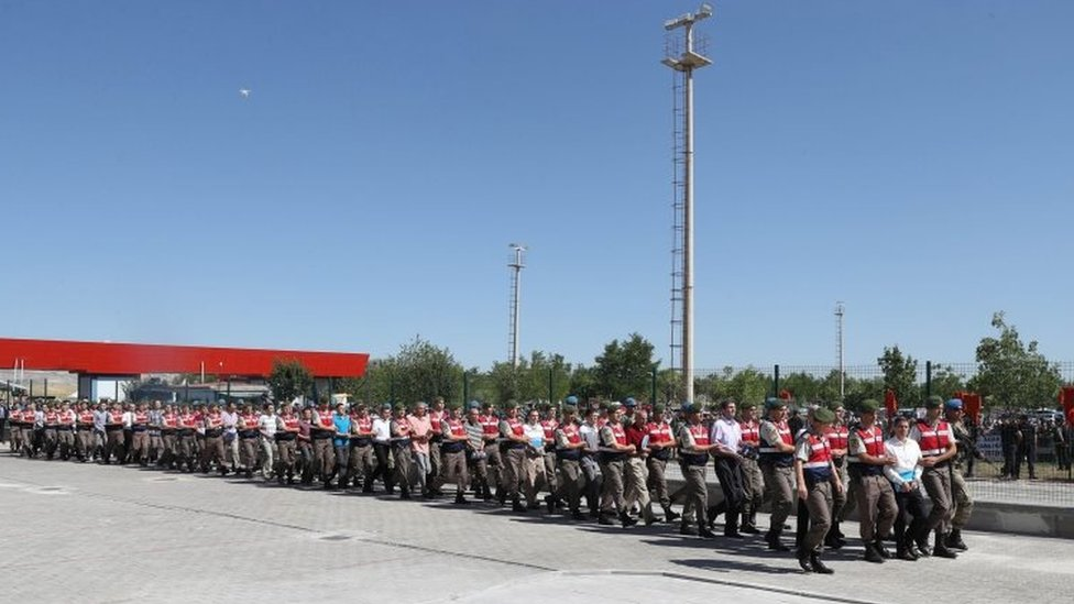 The line of defendants arriving for their trial (01 August 2017)