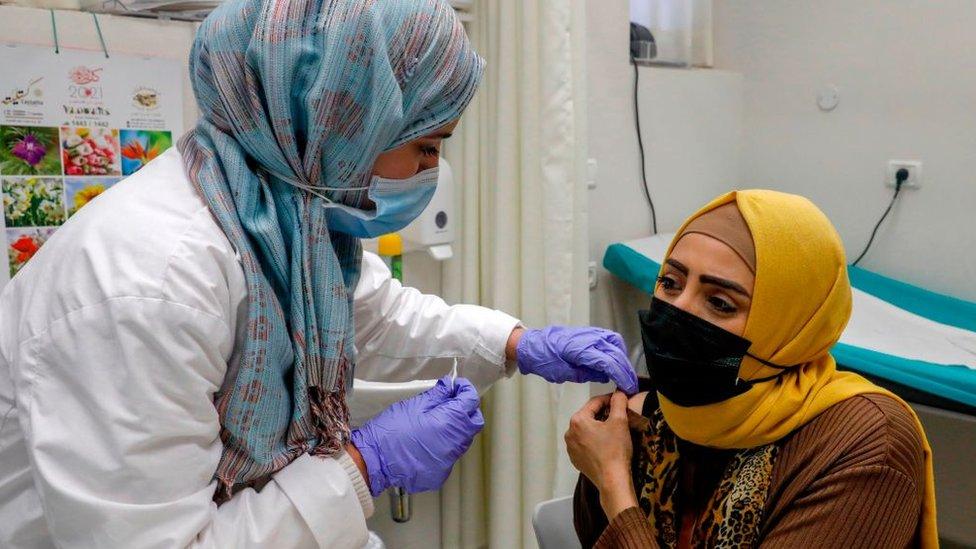 Una mujer palestina recibe una vacuna de covid