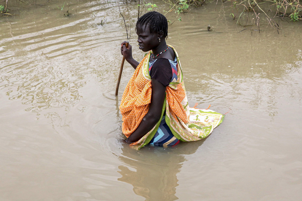 A South Sudanese woman walks in a flooded area that has been isolated for about a month and a half due to the heavy rain in Pibor Town, Boma state,