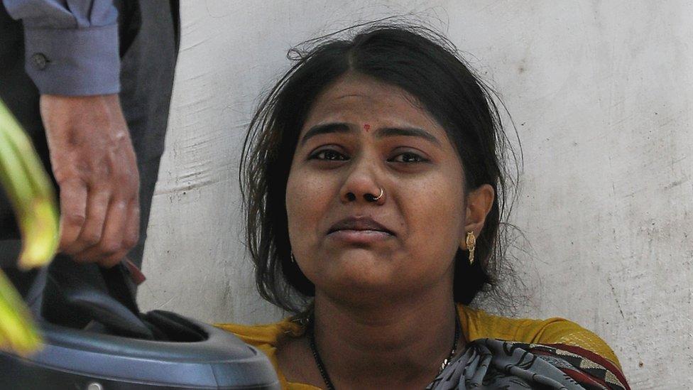 Uma mulher chorando do lado de fora de um crematório