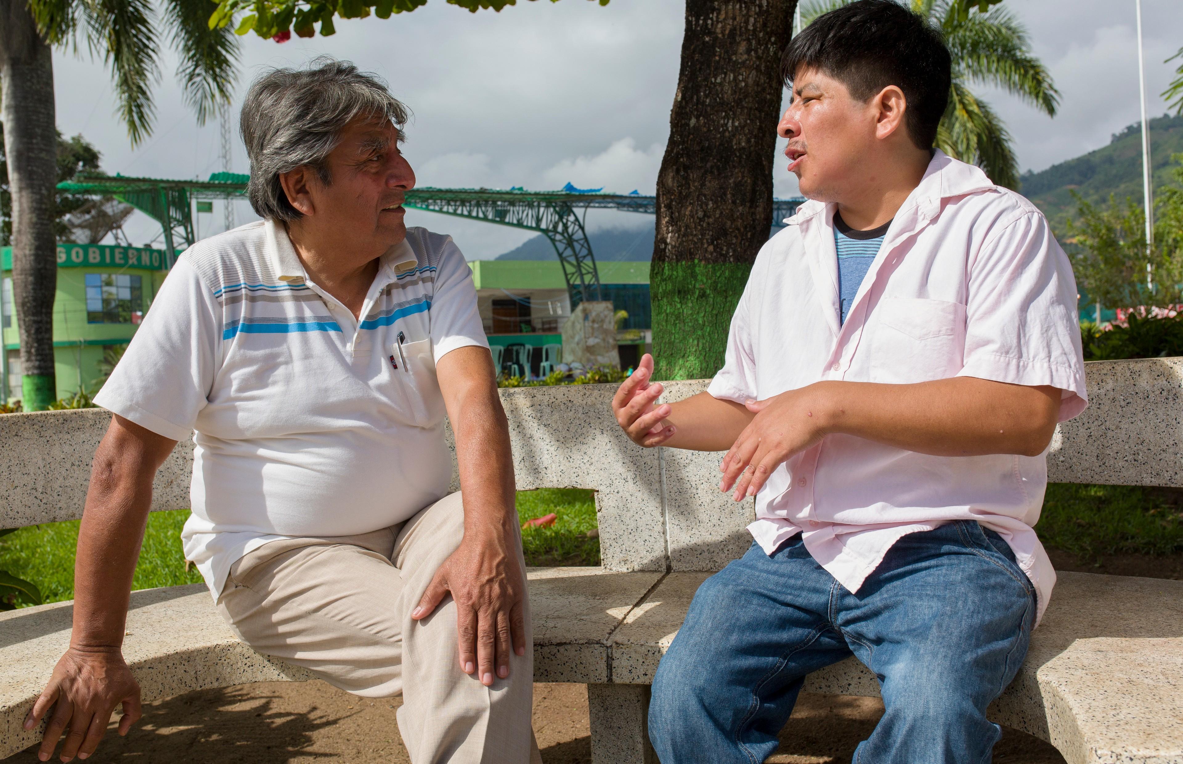El Dr. Roger Zapata y Luis Fermín Tenorio Cortez en 2018 sentados en el banco de una plaza en Pichanaki conversando