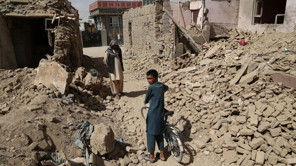 Un hombre y un niño afganos en medio de casas destruidas tras el ataque talibán en Ghazni el pasado mes de agosto.