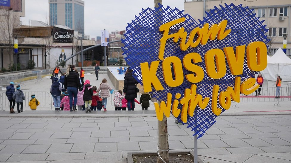 A sign saying 'From Kosovo with Love' stands on a street with children in the background.