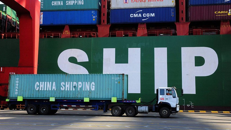 A truck carries a container past a ship at the port in Qingdao, in China's Shandong province