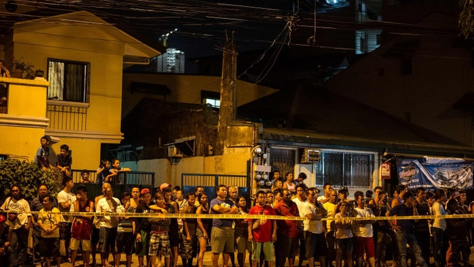 Residents of a Manila district at the scene of a shootout that left two suspected drug dealers dead