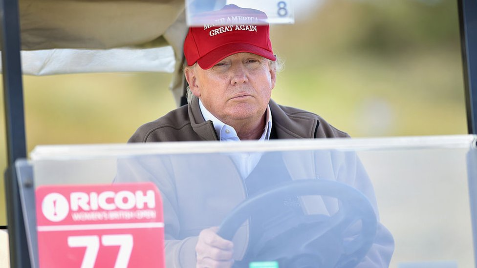 Donald Trump sits behind the wheel of a golf cart.