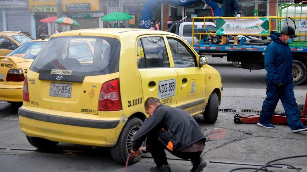 Taxista cambia llanta