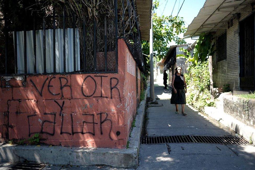 """Mujer pasa junto a una pintada que dice """"ver, oír y callar"""" en Las Margaritas, Soyapango, El Salvador, el 29 de octubre de 2010."""