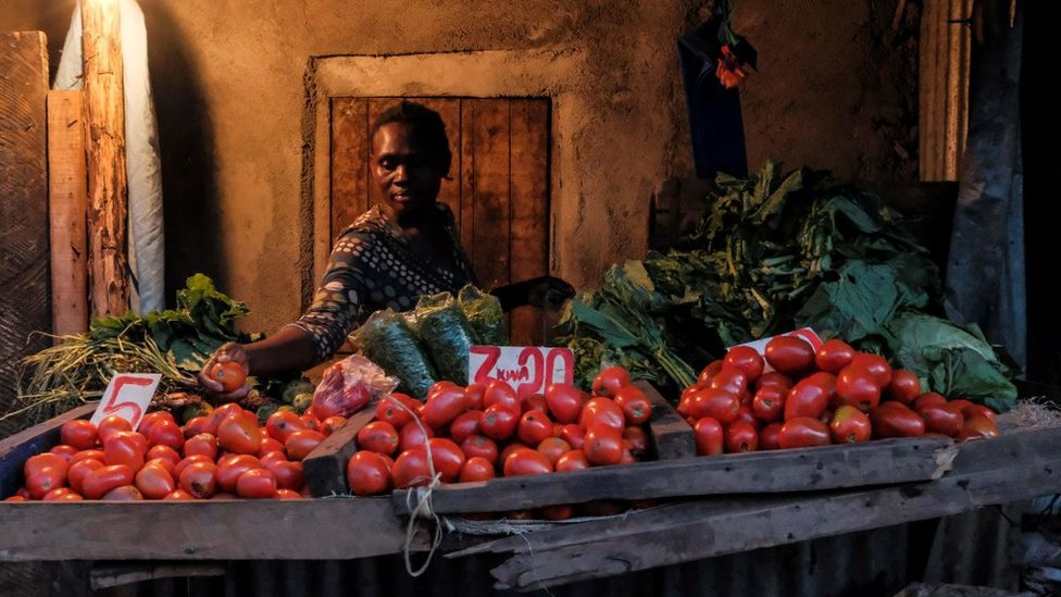 A woman makes a selection of the most expensive tomatoes for a customer just before the 7PM curfew in Kibera, Nairobi on May 05, 2020.