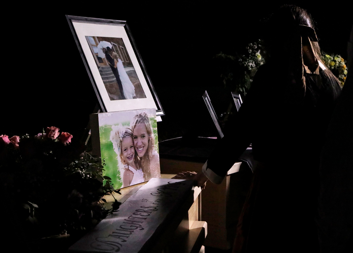 A girl looks at the coffins with the remains of Rhonita Miller and four of her children