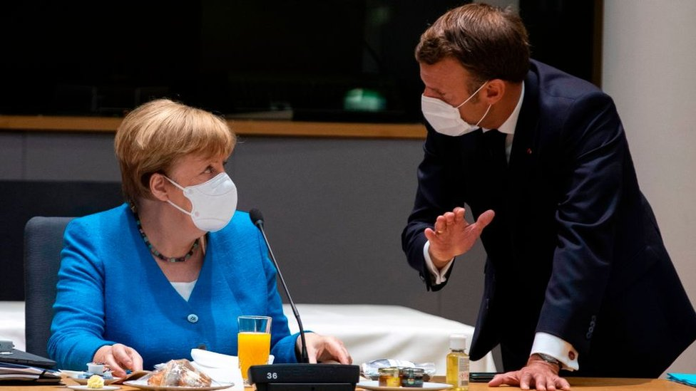 Germany's Chancellor Angela Merkel (L) talks with France's President Emmanuel Macron prior the start of the EU summit at the European Council building in Brussels, on July 18, 2020
