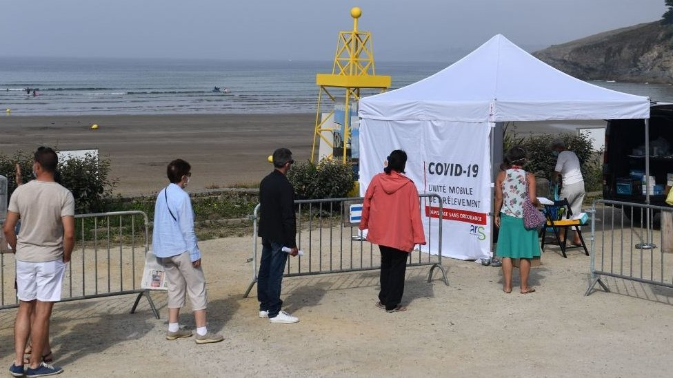 People wait to be tested at a mobile test centre on a beach in western France,