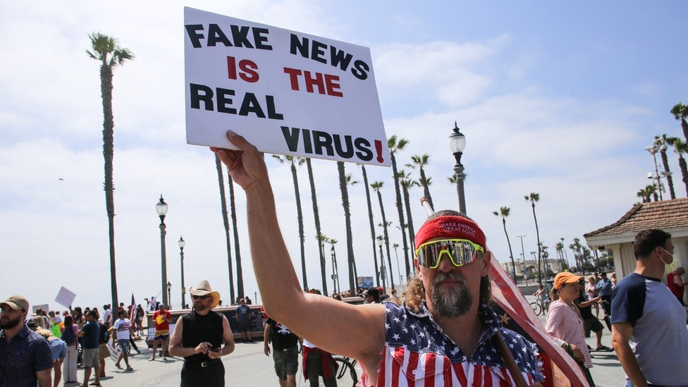 "A man holds a sign during a demonstration in California in early May saying ""Fake news is the real virus"""